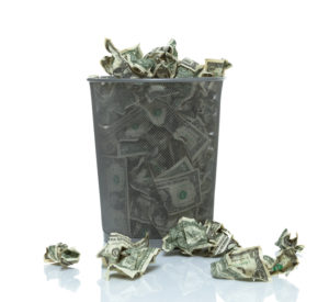 Trash can overflowing with money being thrown away