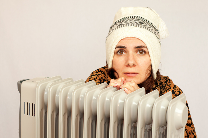 Freezing young woman near a heater